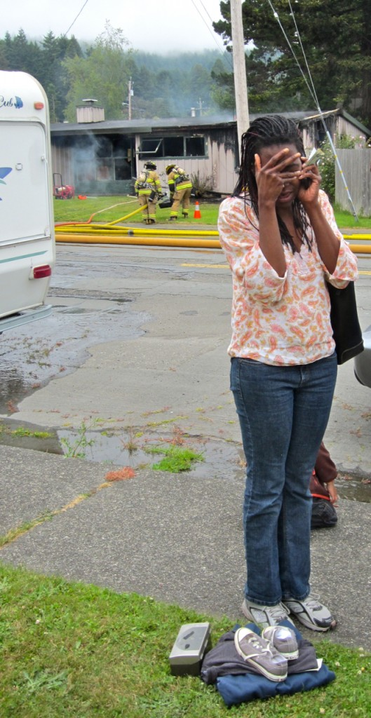 Melinda McCarin grieves the loss of her home as the fire is put out. KLH | Ee