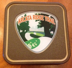 Five of these collectible Arcata Ridge Trail markers, with the logo designed by Dave Held, will be available for $65 each.